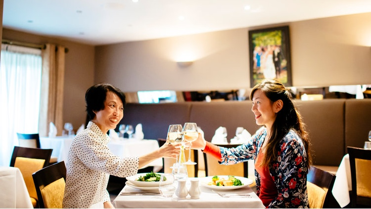 A Chinese mother and daughter sitting at a table, enjoying an evening meal at Bicester Hotel restaurant.